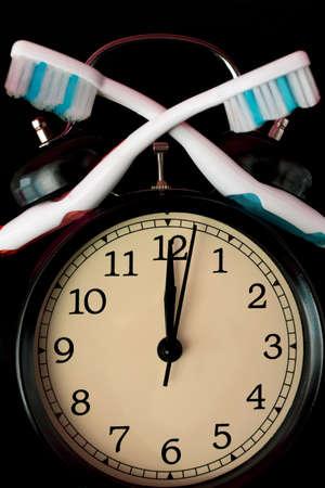 Dental hygiene time concept. Black alarm clock with black background. Imagens