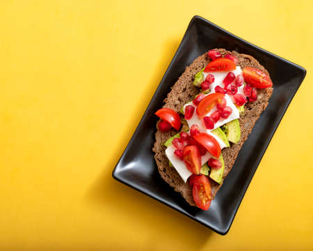 Healthy food concept. Slice of bread with avocado, cherry tomatoes and fresh cheese
