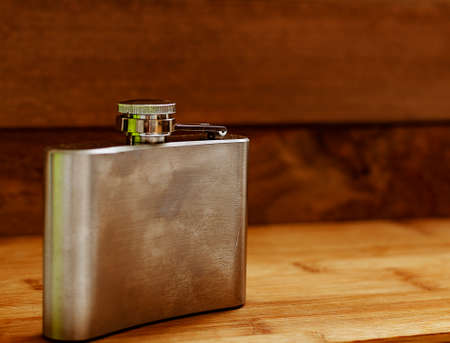 Liquor flask made of metal on a wooden background.