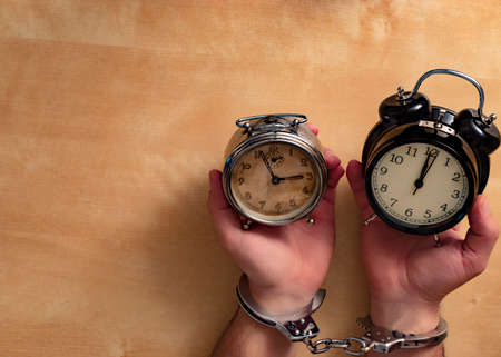 Old and new concept. Two alarm clocks fastened with hands enamped. Stockfoto