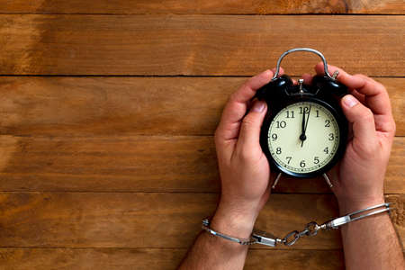 Time in jail. Shackled hands holding an alarm clock on a wooden table. Stock Photo