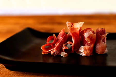 Serrano ham chips on a plate over old wood.