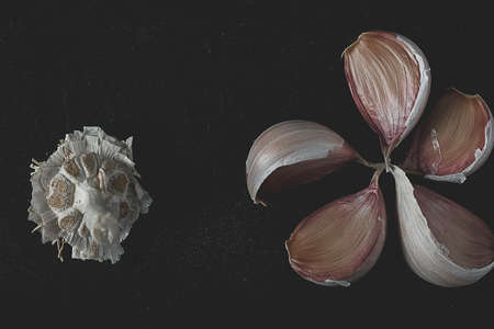 Cloves of garlic on a black vintage background. Фото со стока