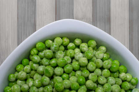 Green peas - desaturated background - in a white dish with the background in black and white.