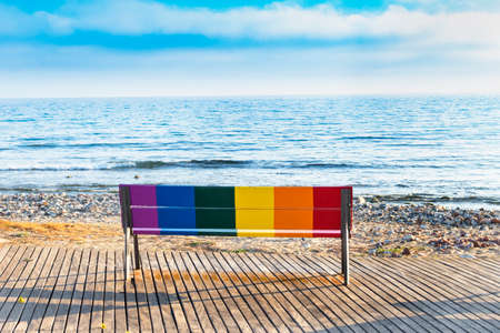 LGBT icon bench in front of the beach painted with the colors of the LGBT flag.