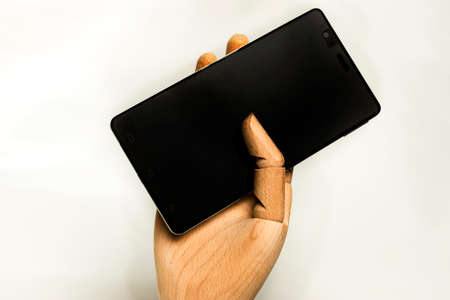 Wooden hand fastened a black mobile phone with white background.