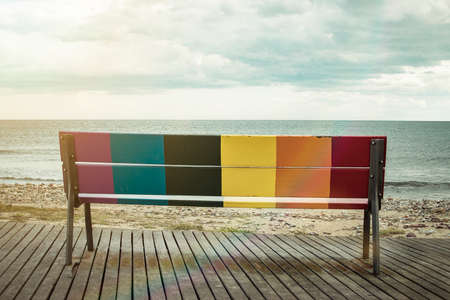 Rainbow LGBT pride flag painted on a wooden bench on the beach with the sea in the background. Banco de Imagens
