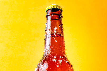 Very cold beer bottle with ice and cold drops on its outside, exposed with yellow background.