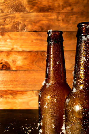 Two bottles of ice cold beer fresh out of the fridge, with a rustic wooden background.