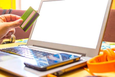 Espacio de trabajo conceptual, portátil con pantalla en blanco sobre la mesa, con tarjeta de crédito y móvil.