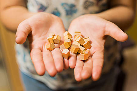 Womans hands holding a pile of wooden toy houses. Stock fotó