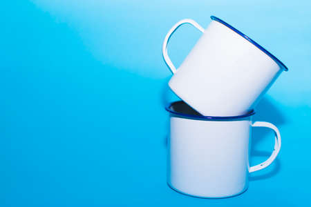 Space to put text. Two white metal cups on a blue background.