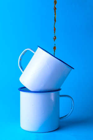 Serving coffee on two white metal cups on blue background.