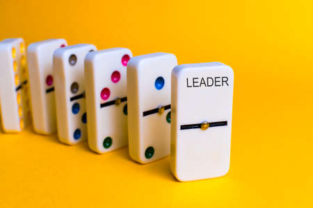 Dominoes that follow an order and a token as leader. Leadership concept