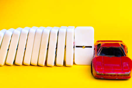 Car insurance concept. Dominoes falling and stopping the domino effect a chip that protects the car.