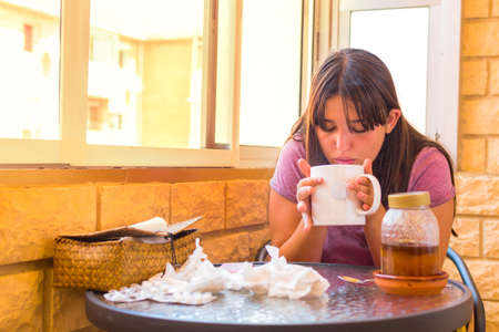 Cold girl blowing a hot drink to cure a cold. Stock Photo