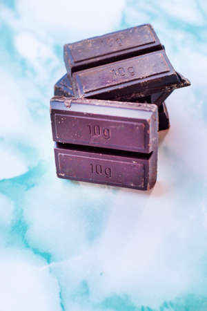Ounce of ten grams of dark chocolate, on a background of blue marble. Stok Fotoğraf