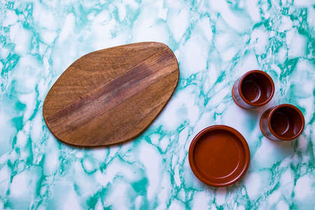 Blue marble background with wood for cutting and clay glasses.