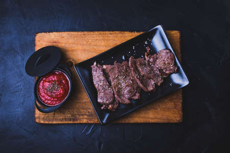 Sliced grilled beef steak. Beef steak with tomato sauce on the cutting board on dark wooden background. Фото со стока