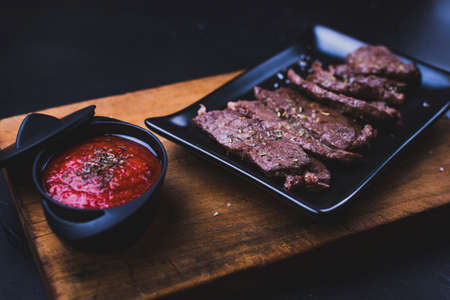 Beef steak sliced. Beef steak cut into strips on a cutting board with tomato sauce on the side. Фото со стока