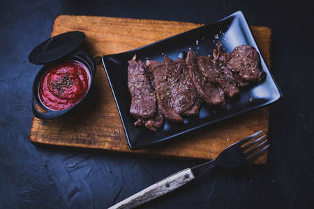 Beef steak cut into strips on a cutting board with tomato sauce next to it and with kitchen utensils.