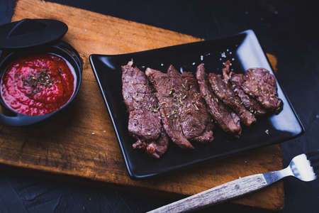 Sliced grilled beef steak. Beef steak with tomato sauce on the cutting board on dark wooden background. 免版税图像