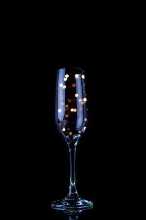 Party concept Glass of champagne with light pearls inside with black background.