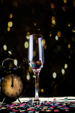 Party concept. Glass of champagne with an alarm clock marking twelve oclock.