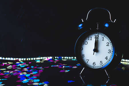 End of the year concept. Alarm clock with confetti with black background. Stockfoto