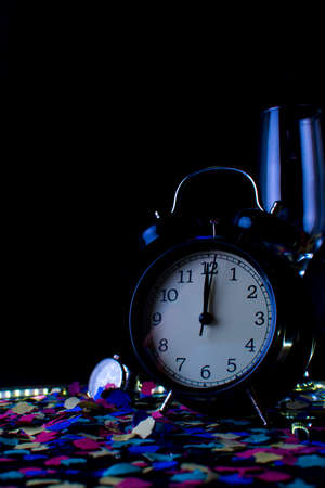 End of the year concept. Alarm clock with confetti and a glass of champagne with the black background.