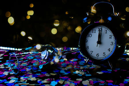 End of the year concept. Alarm clock with confetti with black background. Stock Photo
