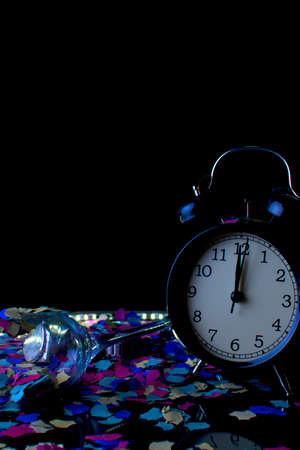 Alarm clock with confetti duels with black background. Party concept until late.