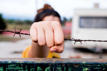A girl's hands raised on the barbed wire. Hunger for freedom.