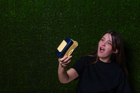 Surprised girl with black T-shirt looking with virtual reality glasses and green background