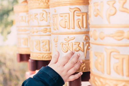Group of golden prayer wheels typical of Buddhist temples moved by a child's hand.