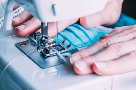 Woman sewing masks in the sewing machine for the COVID-19 pandemic.