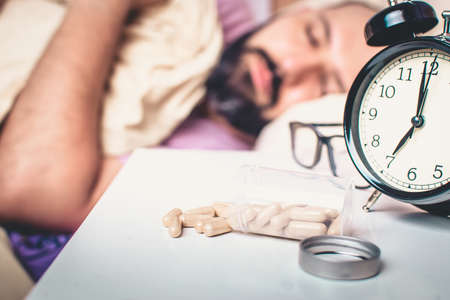 Insomnia concept. Pills to sleep on a nightstand next to an alarm clock, with a doirmido man in the background.