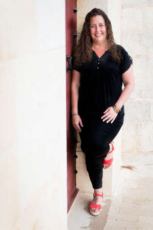 Curvy woman looking left leaning against the wall. Stock Photo
