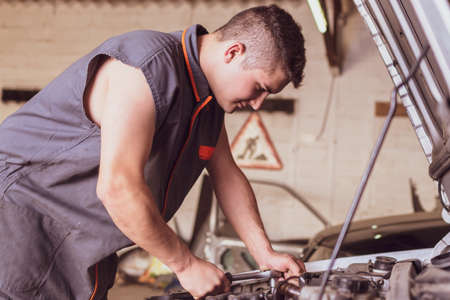 Mechanic in overalls working with a wrench on the car engine.