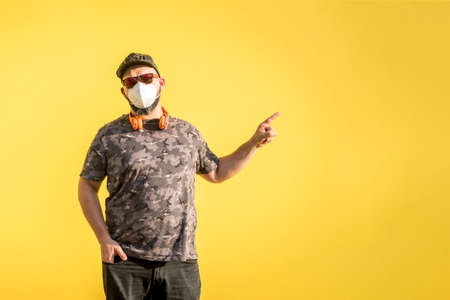 Curvy man with cap, sunglasses and medical mask with disapproval gesture with yellow background.