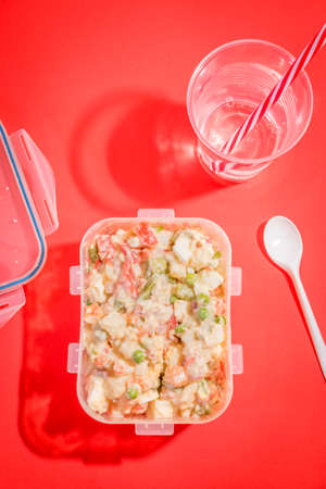 Plastic container with Russian salad and plastic utensils with red background.