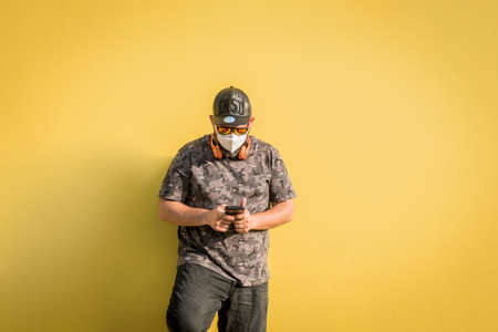 Curvy man with cap, sunglasses and medical mask with the phone and with yellow background.