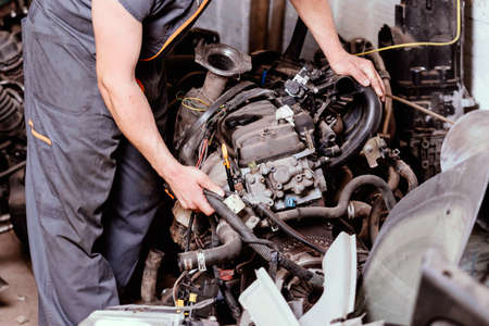 Mechanic looking at the condition of a disassembled car engine.