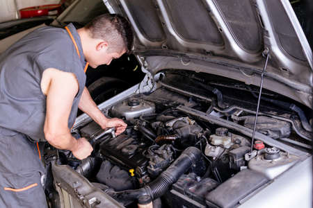 Mechanic working with a wrench on the car engine.