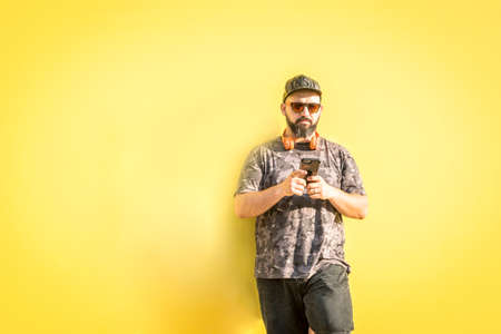 Curvy man with cap and sunglasses chatting on the phone with yellow background.