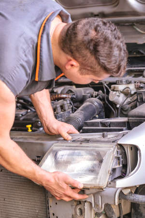 Mechanic repairing the headlight of a car with the gray bodywork.