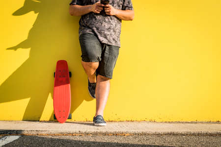 Curvy man with skateboard and yellow background looking at the mobile phone.
