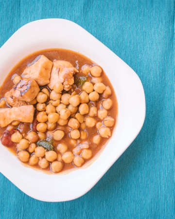 Mediterranean food concept. Food plate with chickpeas, vegetables and chicken pieces with blue cloth background.