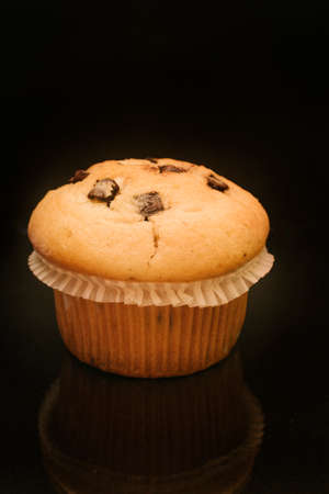 Close-up of homemade cupcake with chocolate shavings with black background. Stock Photo