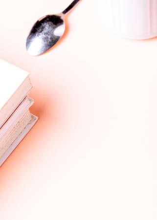 Literature concept. White books with a spoon on pink background.
